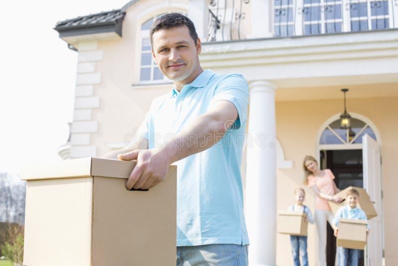 Retrato da caixa de cartão levando do homem seguro ao mover a casa com a família no fundo foto de stock royalty free