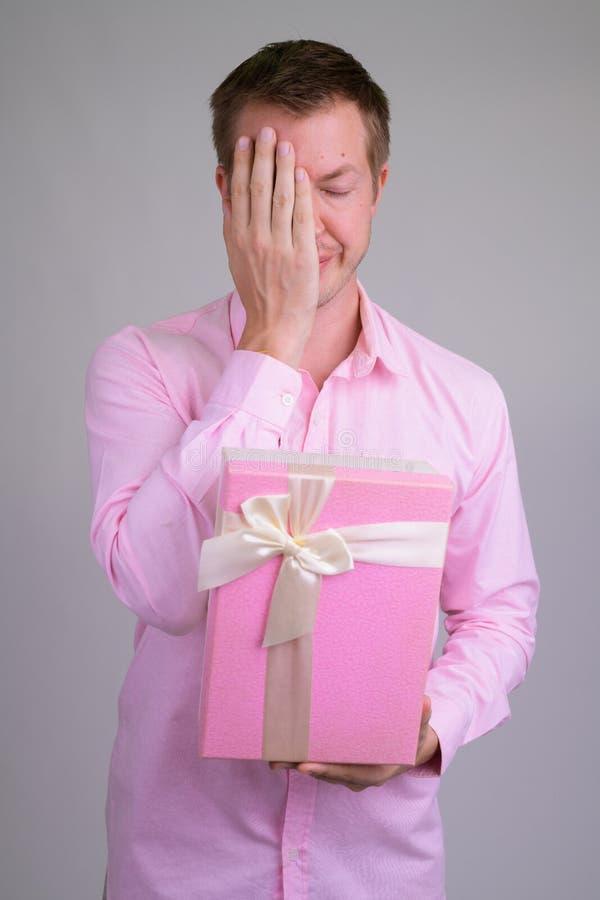 Retrato da caixa de presente da terra arrendada do homem de negócios e da cara novas forçadas da coberta imagem de stock