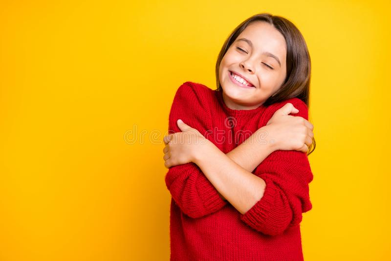 Retrato da calma criança abraçar-se, desfrutar de uma camisola quente e macia que usa um estilo de vida vermelho e estiloso imagens de stock royalty free
