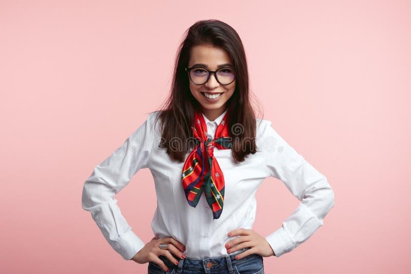 Retrato da camisa branca vestindo, do lenço e dos monóculos da fêmea europeia nova alegre atrativa, sorrindo amplamente sobre foto de stock