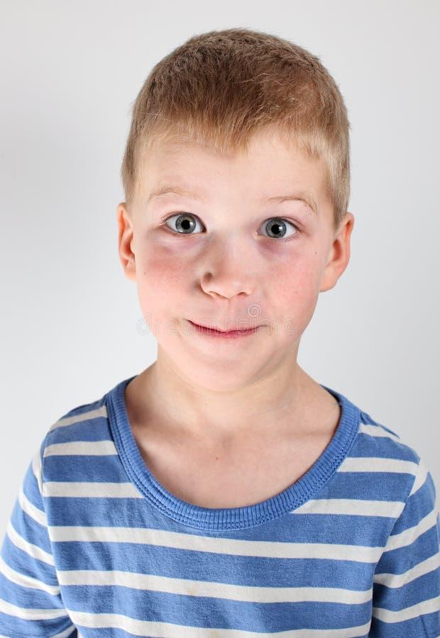 Retrato da camisa listrada do wearinfg louro do menino no fundo branco fotografia de stock