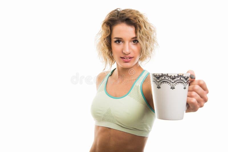 Retrato da caneca de café de oferecimento da menina apta nova bonita fotos de stock