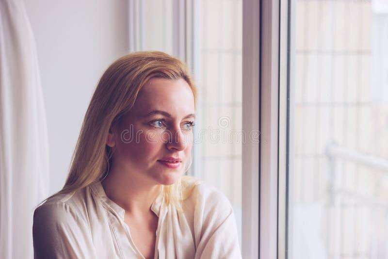 Retrato da cara da mulher da beleza Vista fêmea loura através dos wi fotografia de stock