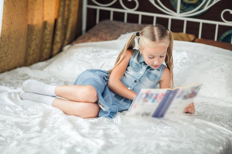 Retrato da casa de uma menina em sundress da sarja de Nimes com o cabelo louro longo que senta-se em uma cama e que lê um livro imagem de stock royalty free