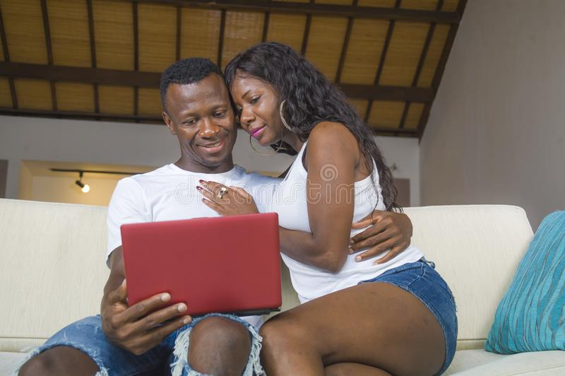 Retrato da casa do estilo de vida de pares afro-americanos pretos felizes e bonitos novos no amor que aprecia no sofá do sofá da  fotos de stock royalty free