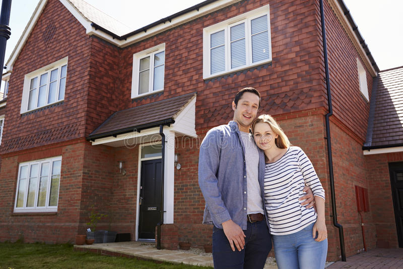 Retrato da casa nova da parte externa ereta nova dos pares fotografia de stock royalty free