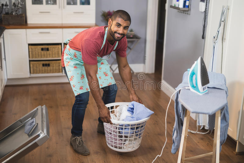 Retrato da cesta de lavanderia de levantamento de sorriso do homem pela tábua de passar a ferro na cozinha imagens de stock