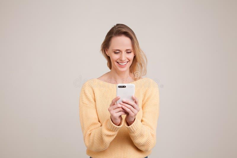 Retrato da cintura-acima da mulher de sorriso loura nova que usa o telefone celular, mensagem, estando feliz conversar com seu no imagens de stock royalty free