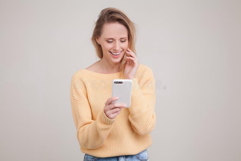 Retrato da cintura-acima da mulher de sorriso loura nova que usa o telefone celular, mensagem, estando feliz conversar com seu no imagens de stock