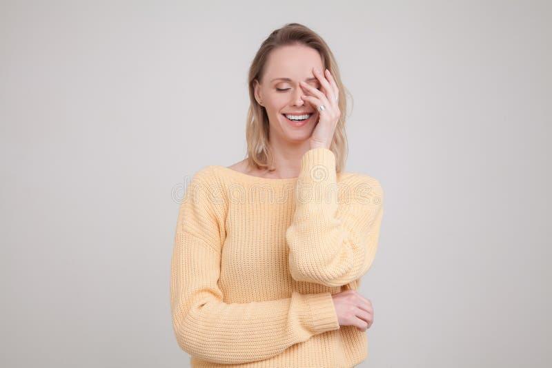 Retrato da cintura-acima da mulher loura feliz com express?o satisfeito em sua cara, com os olhos fechados, mantendo sua m?o na c fotografia de stock
