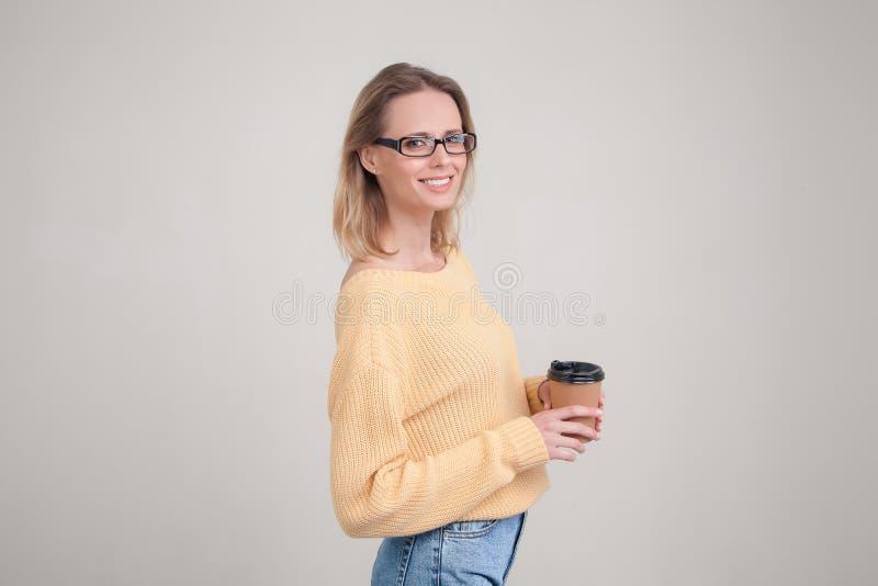 Retrato da cintura-acima da mulher loura que guarda o tamp?o do caf? em suas m?os e que sorri, olhando a c?mera camiseta amarela  foto de stock