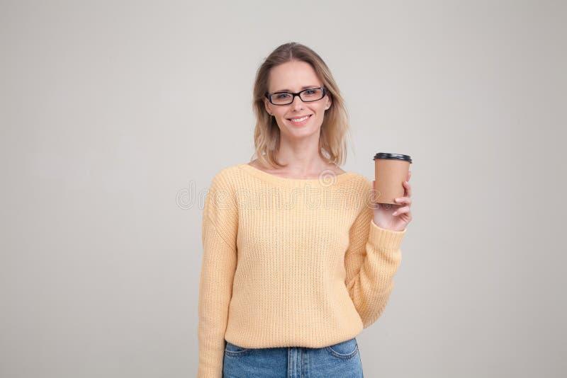 Retrato da cintura-acima da mulher loura que guarda o tamp?o do caf? em suas m?os e que sorri, olhando a c?mera camiseta amarela  fotografia de stock royalty free