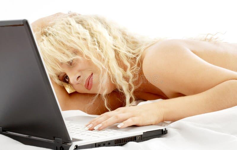Retrato da colocação loura na cama com portátil fotografia de stock royalty free