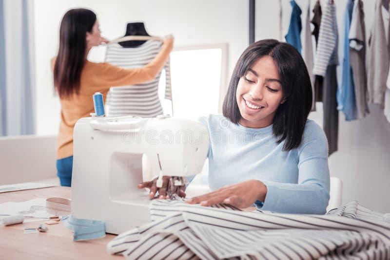 Retrato da costureira positiva que costura um vestido imagem de stock