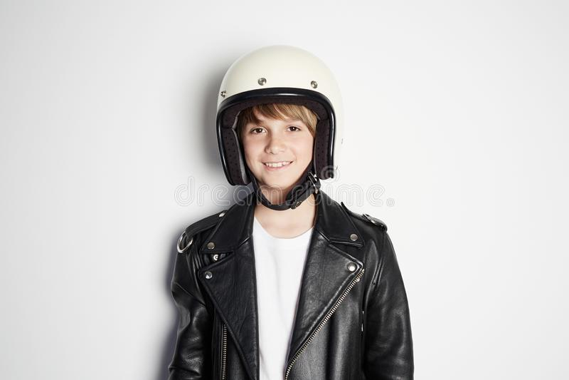 Retrato da criança adolescente bonita feliz nova no casaco de cabedal preto e no capacete branco do moto que sorri no fundo branc imagem de stock
