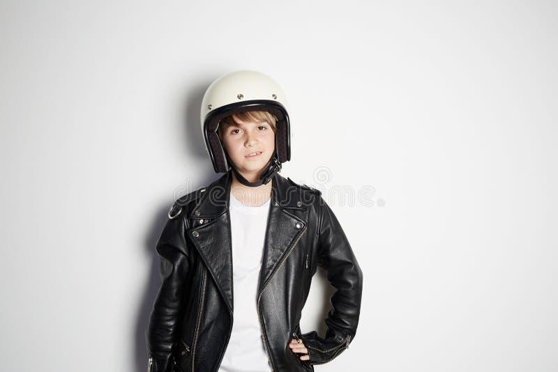 Retrato da criança adolescente bonita fresca nova no casaco de cabedal preto e no capacete branco do moto que sorri no fundo bran imagem de stock