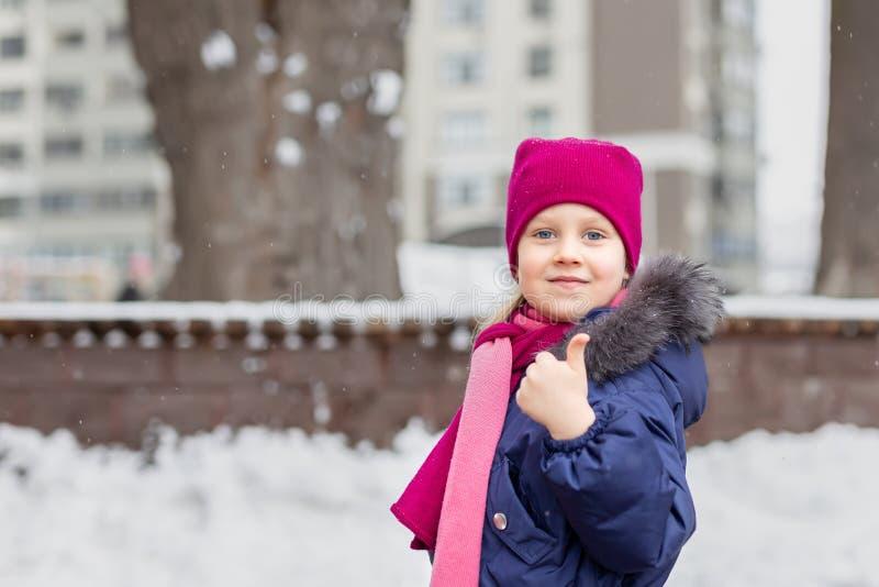 Retrato da criança adorável feliz que mostra os polegares acima do sinal Menina caucasiano pequena bonito no chapéu e no lenço e  imagem de stock
