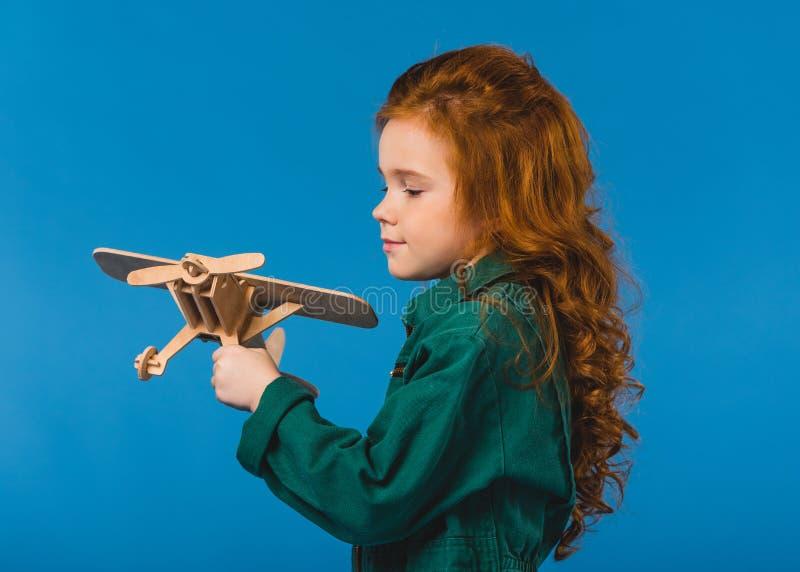 retrato da criança adorável no traje piloto com o brinquedo plano de madeira fotografia de stock