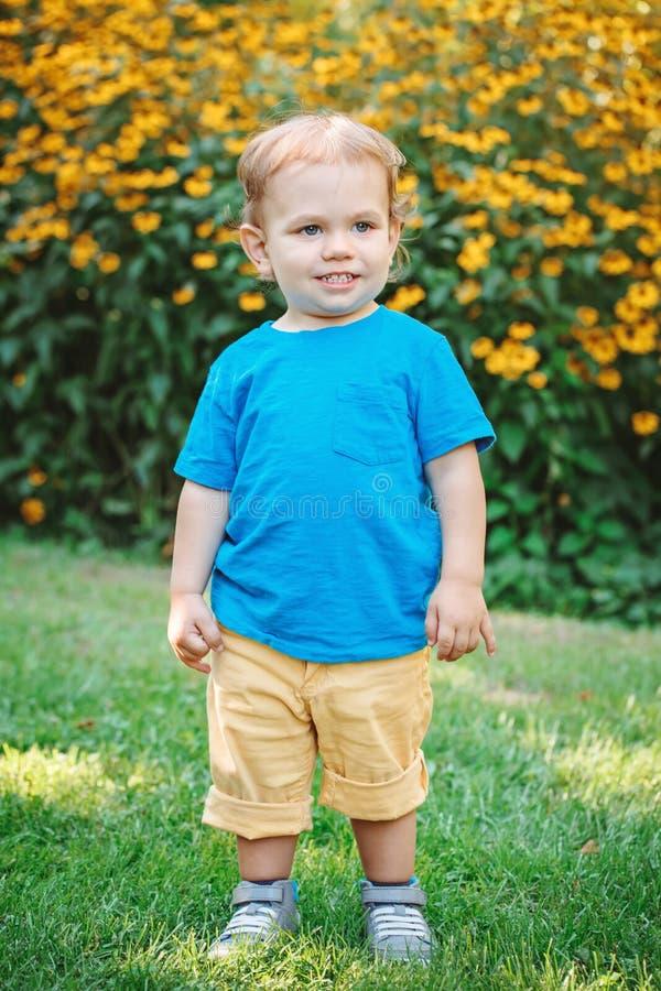 Retrato da criança caucasiano branca de sorriso de riso adorável bonito do bebê que está entre flores amarelas fora no parque do  fotos de stock royalty free