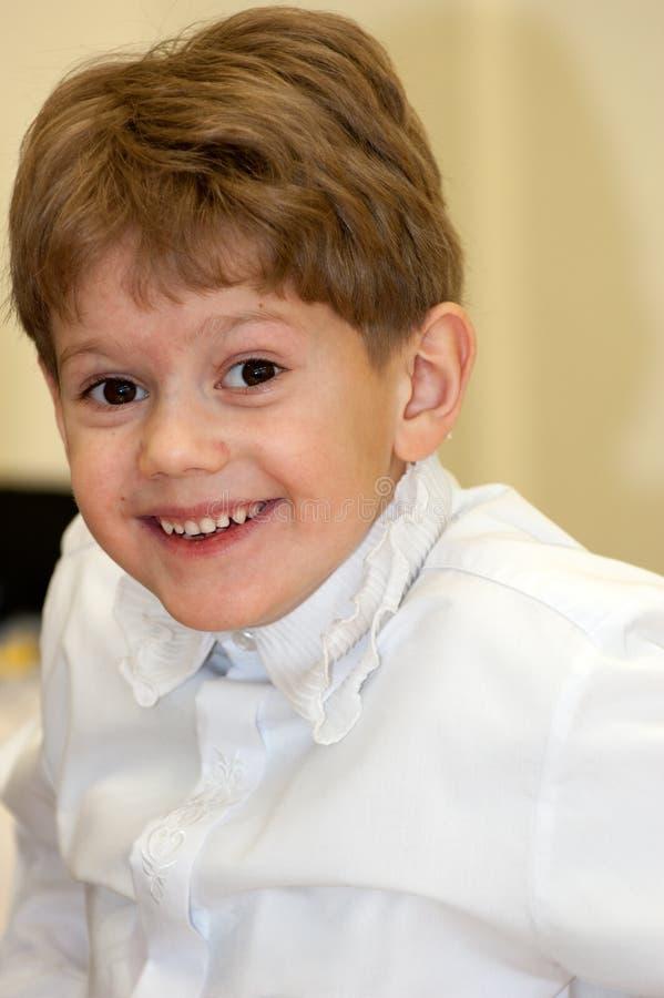 Retrato da criança caucasiano engraçada adorável bonito do rapaz pequeno na camisa branca que sorri fazendo as caras que têm o di imagens de stock royalty free