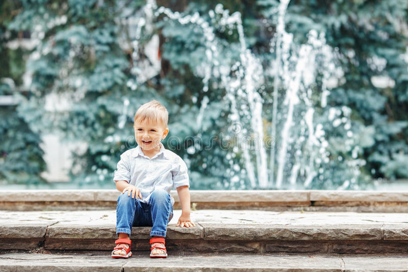 Retrato da criança caucasiano engraçada adorável bonito do rapaz pequeno na camisa e na calças de ganga brancas imagem de stock