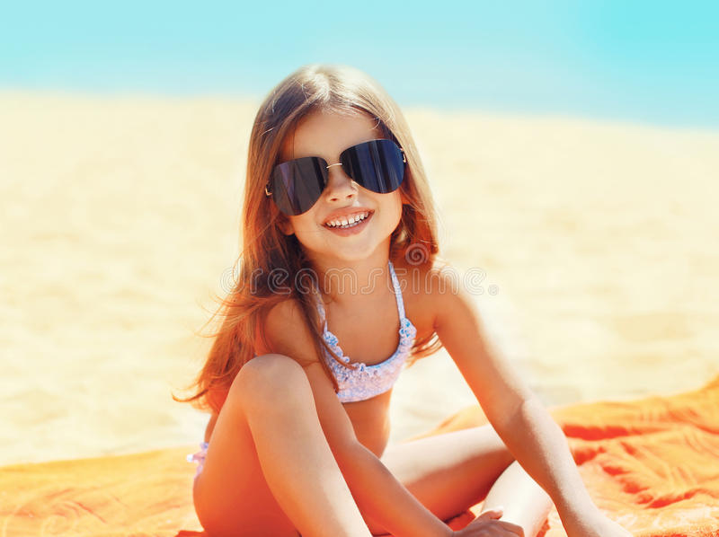 Retrato da criança da menina nos óculos de sol que relaxam na praia imagens de stock royalty free