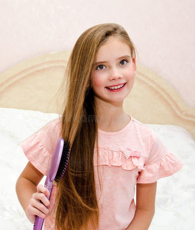 Retrato da criança de sorriso bonito da menina que escova seu cabelo imagem de stock