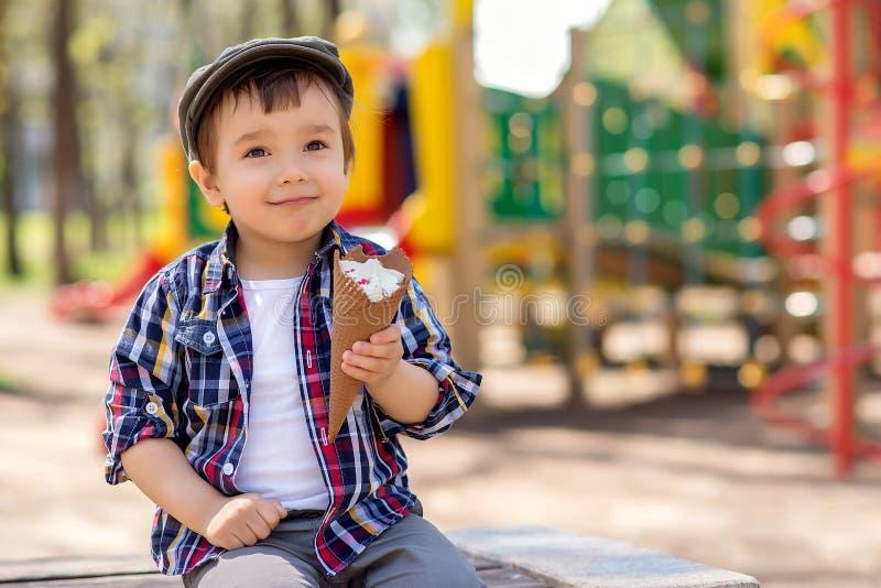 Retrato da criança de sorriso com a expressão visionário da cara que senta-se no banco com gelado no cone do waffle no dia ensola imagens de stock royalty free