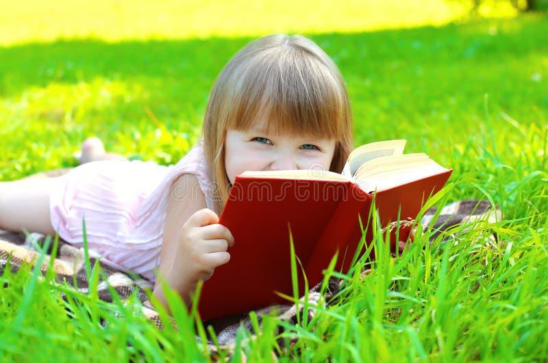 Retrato da criança de sorriso pequena da menina com o livro que encontra-se na grama fotografia de stock