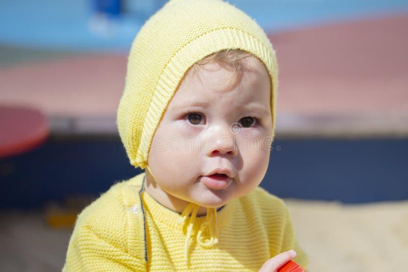 Retrato da criança em uma caminhada, cara do close-up Menino do bebê 11 meses velho em um terno feito malha amarelo foto de stock