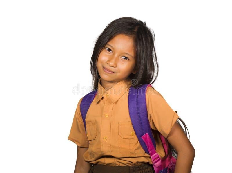 Retrato da criança fêmea feliz e entusiasmado bonita na farda da escola que leva alegre de sorriso do saco do estudante isolada n imagem de stock royalty free