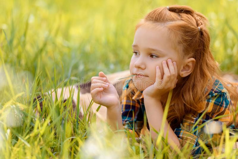 retrato da criança pensativa pequena que descansa na grama verde fotos de stock royalty free