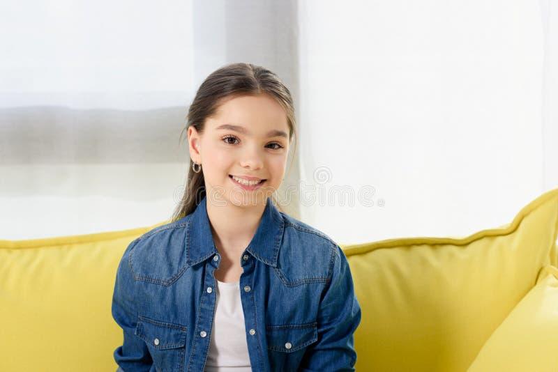 retrato da criança preteen de sorriso que olha a câmera no sofá imagens de stock