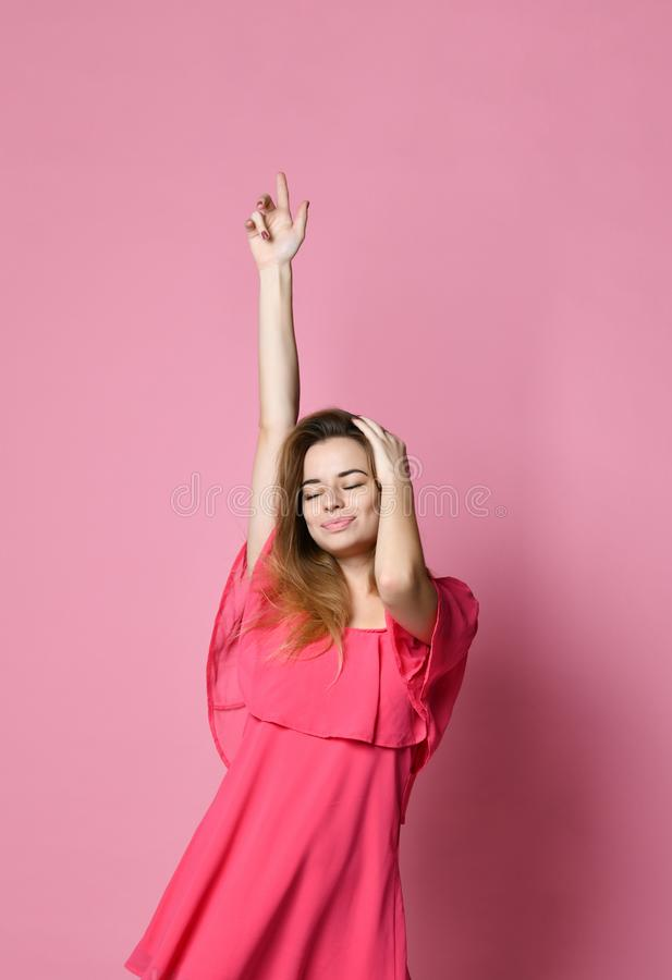 Retrato da dança caucasiano moreno da menina contra a parede cor-de-rosa que exulta o bom humor foto de stock