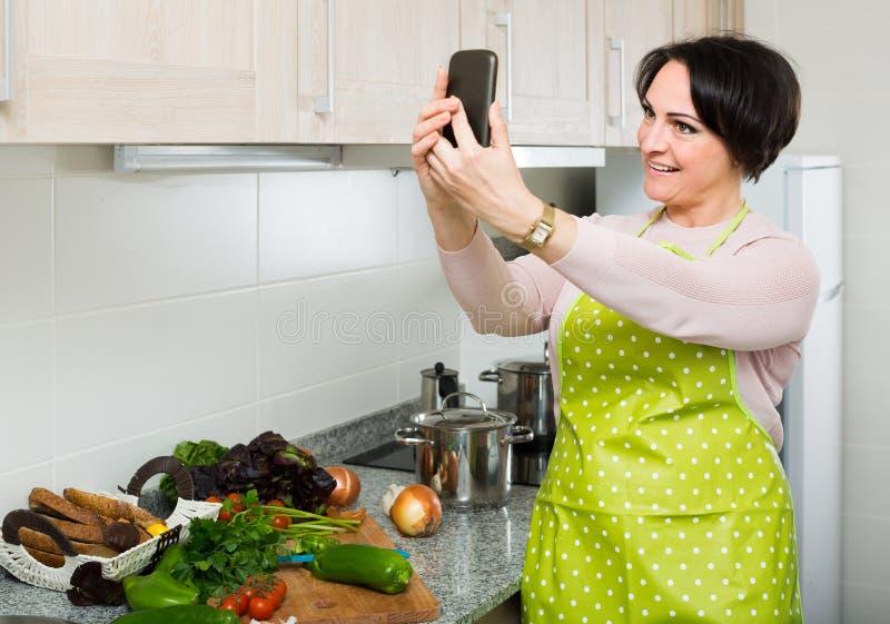 Retrato da dona de casa no avental que faz o selfie na cozinha doméstica imagem de stock