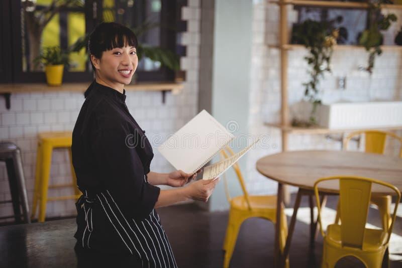 Retrato da empregada de mesa nova que guarda o menu ao inclinar-se na tabela imagens de stock