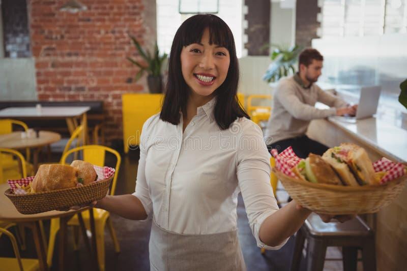 Retrato da empregada de mesa que guarda cestas com sanduíches quando homem de negócios que usa o portátil imagem de stock royalty free