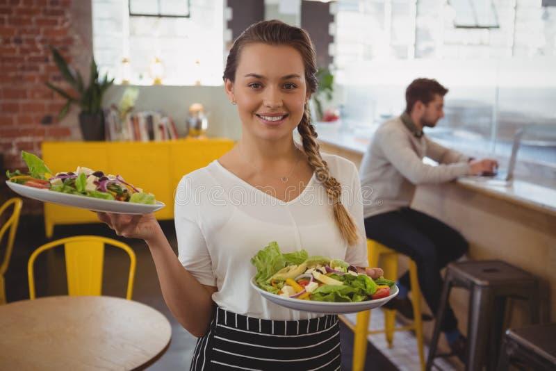 Retrato da empregada de mesa que guarda placas com salada quando homem de negócios que usa o portátil fotos de stock