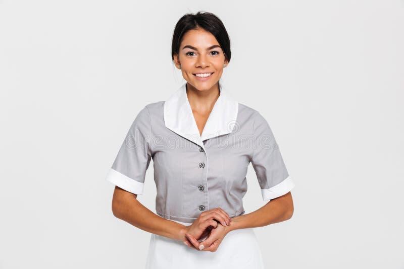 Retrato da empregada doméstica de sorriso bonita no uniforme que mantém o togethe das mãos fotografia de stock royalty free