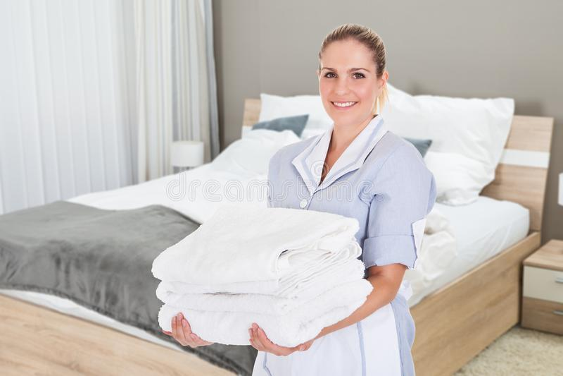 Retrato da empregada doméstica Holding Clean Towels do hotel fotos de stock