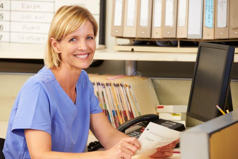 Retrato da enfermeira que trabalha na estação das enfermeiras imagem de stock royalty free