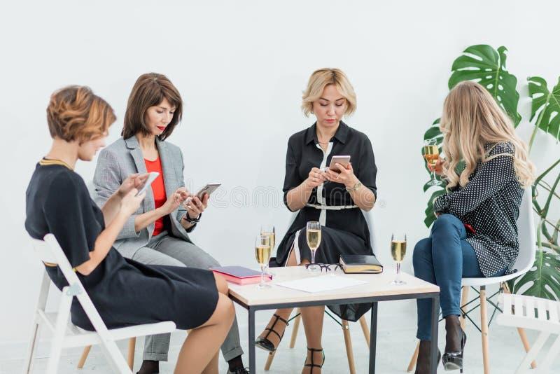 Retrato da equipe fêmea do negócio no estúdio moderno com vidros do champanhe fotografia de stock