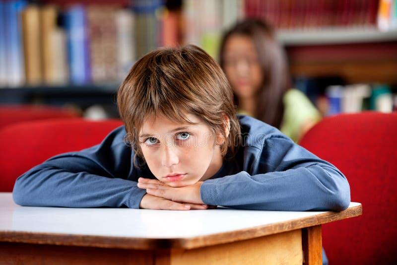 Retrato da estudante furada que inclina-se na tabela dentro imagens de stock royalty free