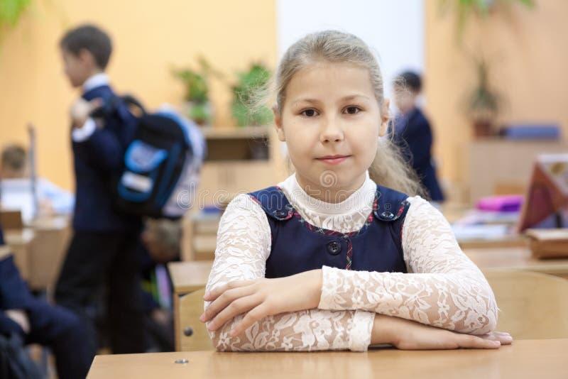 Retrato da estudante que senta-se na mesa na sala de aula no rebaixo quando o outro jogo dos alunos imagens de stock