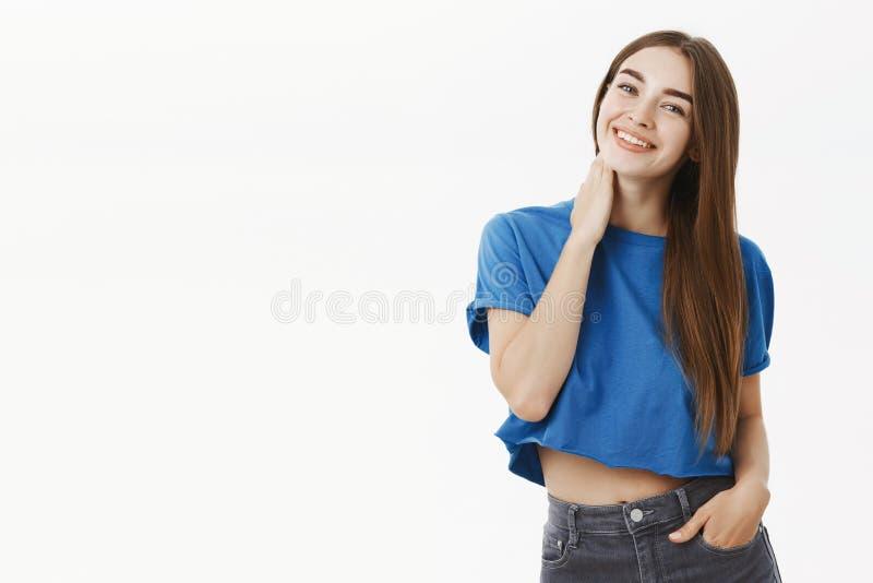 Retrato da fêmea bonito macia e feminino na cabeça de inclinação tímida e flirty tocante colhida do pescoço do t-shirt azul e fotografia de stock royalty free