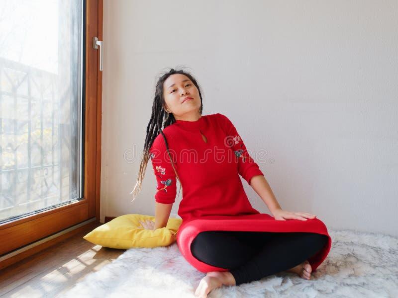 Retrato da fêmea chinesa nova com os dreadlocks bonitos na casa ensolarada isolada com o fundo branco da parede, sentando-se no t foto de stock