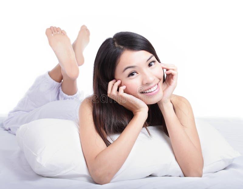 Retrato da face feliz do sorriso da mulher que encontra-se na cama imagens de stock royalty free
