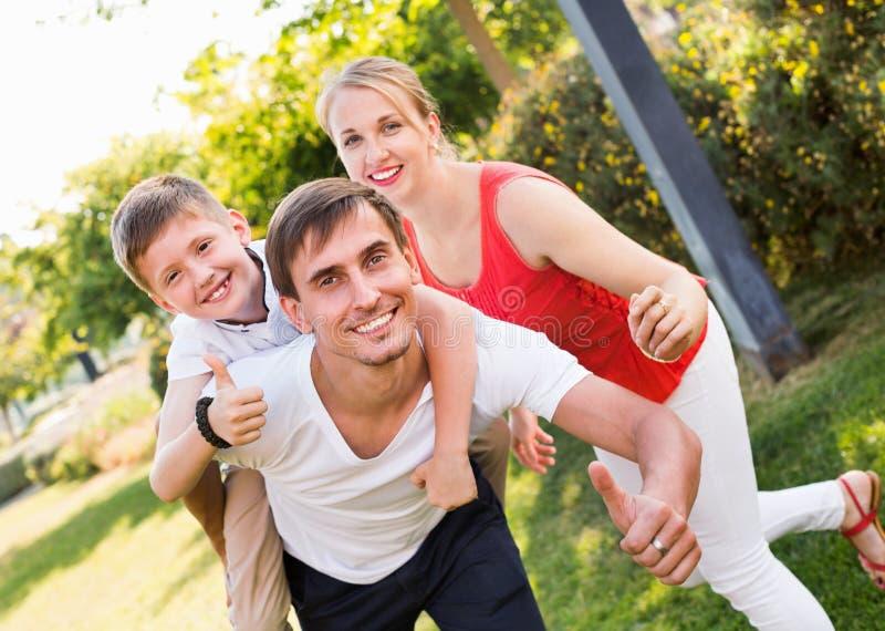 Retrato da família alegre com o menino que senta-se no father& x27; parte traseira de s fotografia de stock royalty free