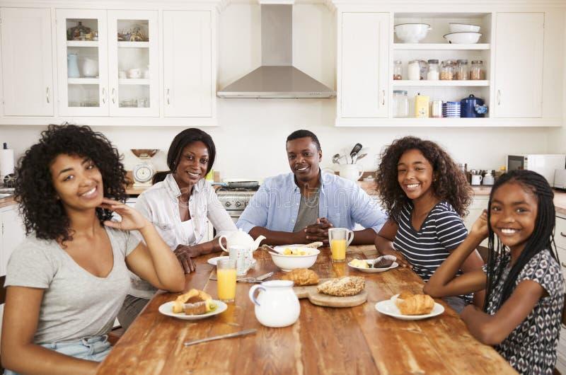 Retrato da família com as crianças adolescentes que comem o café da manhã imagem de stock royalty free