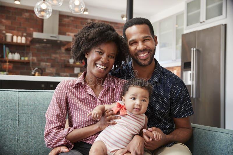 Retrato da família com a filha do bebê que relaxa em Sofa At Home Together fotos de stock royalty free